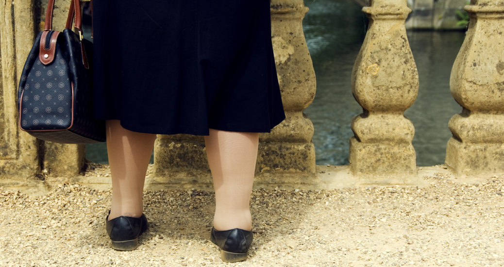 Woman's legs, shoes, handbag and black skirt