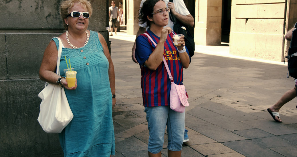 Two women, one older and dressed in green, the other younger and dressed in a red-and-blue sports top, have some refreshments in the shade on a piazza in Barcelona