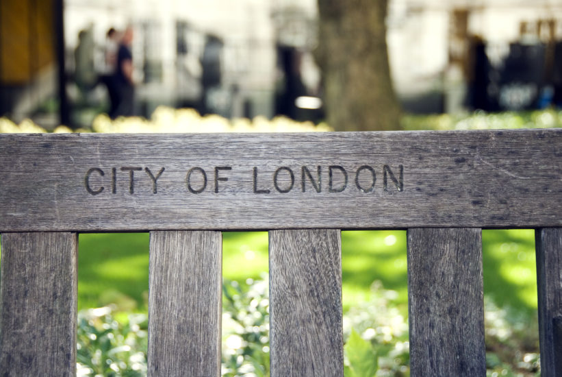 City of London written on a wooden park bench with pedestrians in the distant background