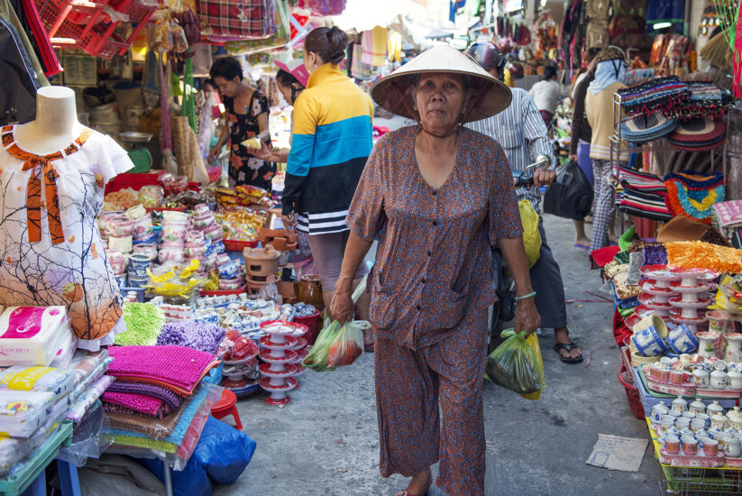 An old woman in traditional Vietnamese outfit shopping at a street market in Ho Chi Minh City
