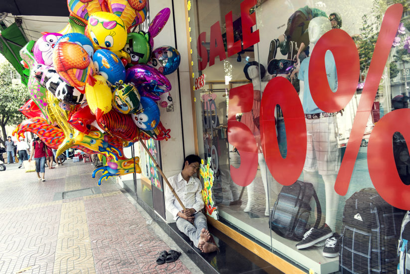 A man holding a bunch of comic helium balloons naps with his head resting against a shopfront advertising a 50% sale