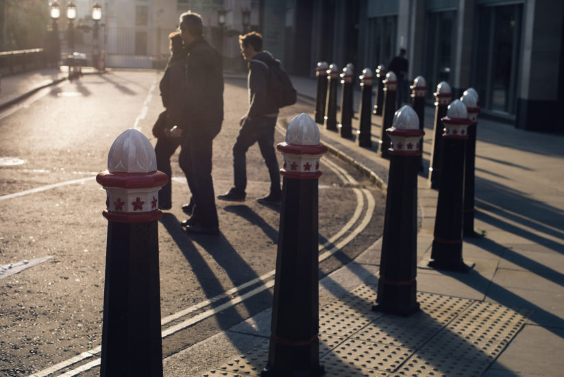 Backlit landscape-orientation shot of three people ambling across a deserted London City street at sunset, with classic emblemed London bollards in the foreground