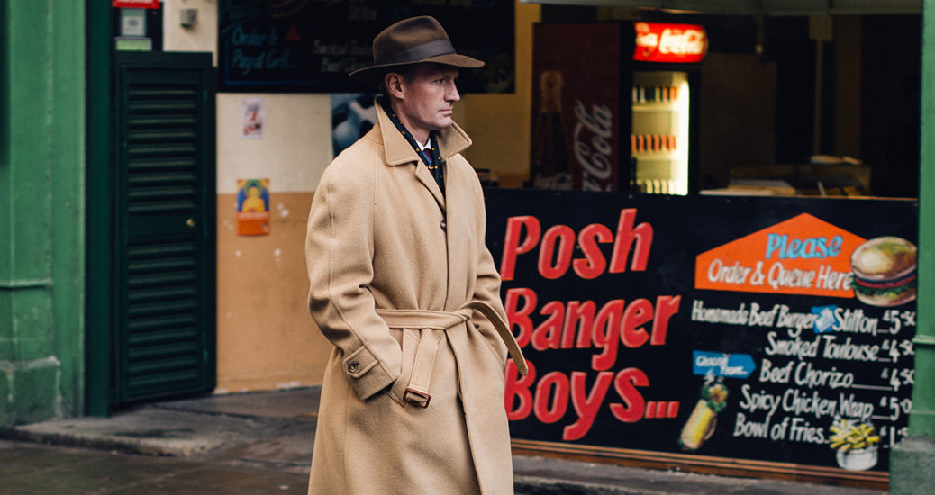 """Medium view of a mysterious man wearing a hat and trenchcoat walking past a shopfront with sign reading """"The Posh Banger Boys"""" in Borough Market, London"""