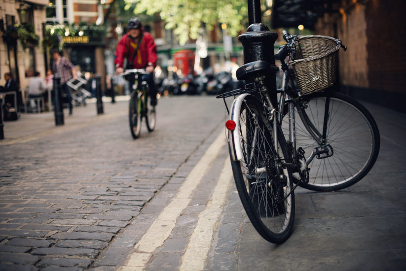 Shallow focus shot of a bike with red tail light and carrier basket parked on the pavement in Soho, London with a man red coat cycling past in the distance