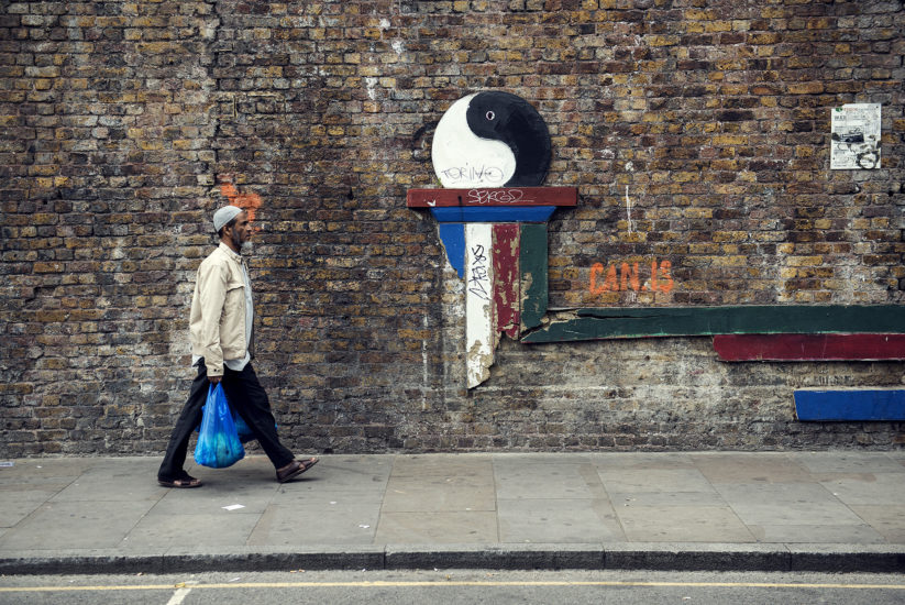 A man wearing a Taqiyah and carrying a blue shopping bag walks past a wall with a giant black-and-white yin-and-yang sign on Brick Lane, London
