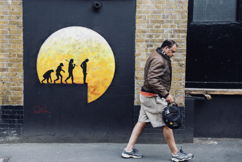 A man walks past a wall with yellow street art depicting humans in different stages of evolution