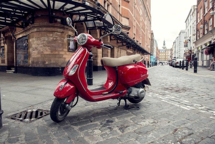 A red Vespa parked on a deserted Soho street