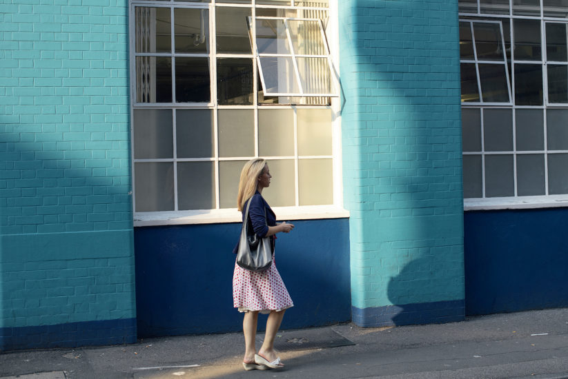 Girl with blue top, handbag and white-and-red skirt walks past a blue wall with metal-frame windows.