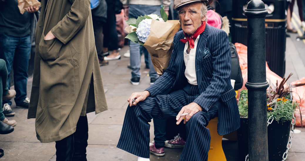 Old man wearing a stylish suit and hat smokes outside a coffee shop on Brick Lane, London