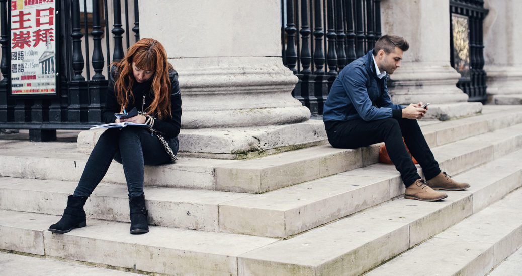 A young man and woman are hunched over there smartphones as they sit, unaware of each other, on the steps of St Martins-in-the-Fields off Trafalgar Square in London