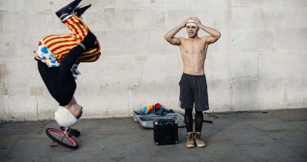A topless trapese artist holds his head in his hands as he watches his companion do a daring somersault on Trafalgar Square in London