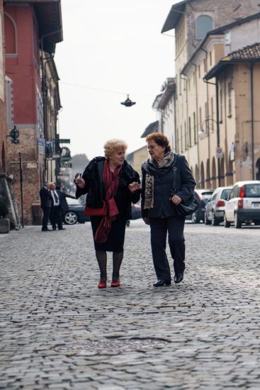 Two old women have an intimate chat as they walk down the street in Cherasco, Langhe region, Italy