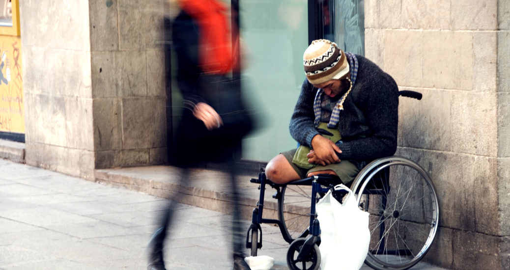 A woman in red scarf and black coat walks past a man in a wheelchair whose legs have both been amputated