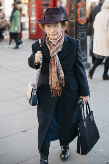 A woman wearing an elegant coat, scarf and hat walks up Charing Cross Road in London