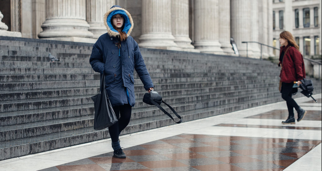 A young woman wearing a blue coat and bright blue hoody walks down the steps of St Paul's Cathedral in London on a cold, wet January afternoon