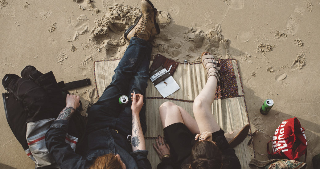 A couple seen from above relax with drinks on The Thames Beach in London at low tide.